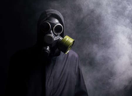 A man in a gas mask in the smoke. black background photo
