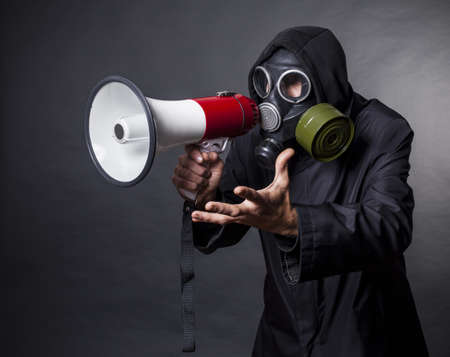 apocalypse: a man in a gas mask with a megaphone calling for help