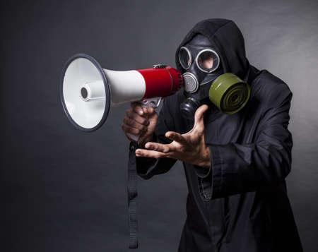 mascara de gas: un hombre con una máscara de gas con un megáfono para pedir ayuda