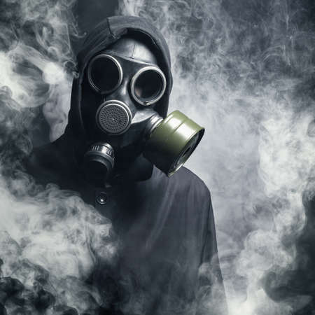 black mask: A man in a gas mask in the smoke. black background Stock Photo
