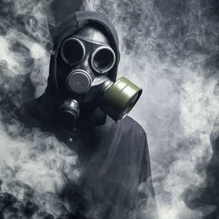 sustancias toxicas: Un hombre con una máscara de gas en el humo. fondo negro