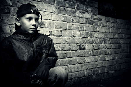 youth culture: portrait of a teenager on a background of an old brick wall