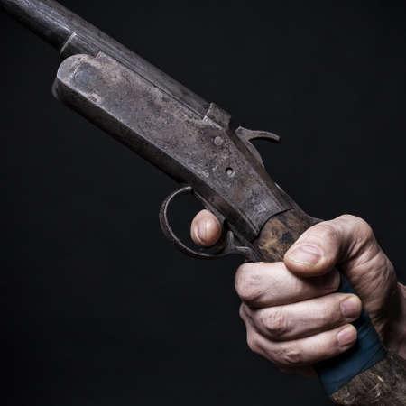 gatillo: hombre sostiene en su mano un fondo shotgun.Black viejo