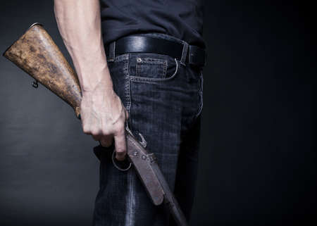 man holds in his hand an old shotgun.Black background Stock Photo - 17955072