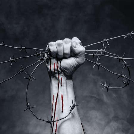 rebeldia: Alambre de púas oxidado en la mano de un hombre fuerte Foto de archivo