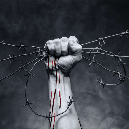 struggling: Rusty barbed wire in a strong mans hand Stock Photo