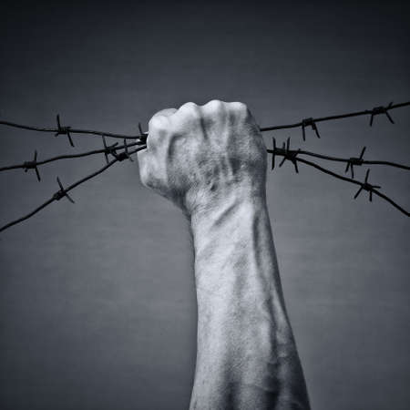 restraining: Rusty barbed wire in a strong mans hand Stock Photo