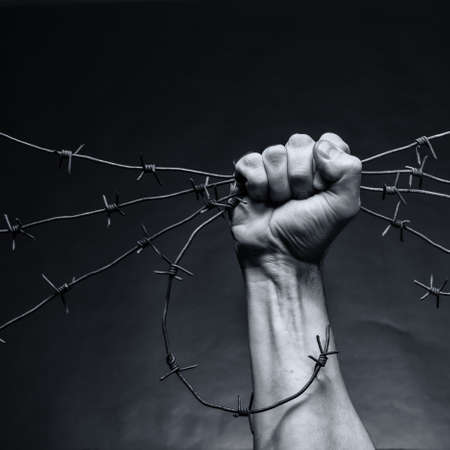 barb: Rusty barbed wire in a strong mans hand Stock Photo