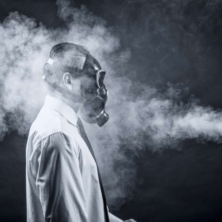 mascara de gas: un hombre con una máscara de gas pasa a través del humo