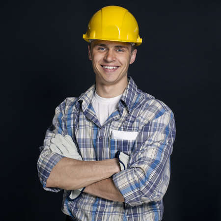 smiling young construction worker on a black background Stock Photo