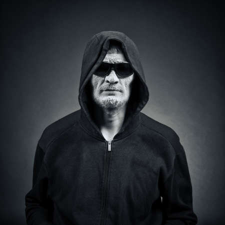 scary man: man in sunglasses and a hood on a dark background