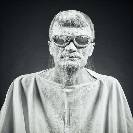 dirty faces: portrait of a man in black glasses.Face in flour