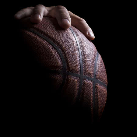 basketball background: Fragment of a basketball ball in a hand of the basketball player