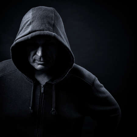 man in a hood on a black background Banco de Imagens