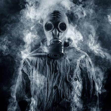 riesgo quimico: Un hombre con una máscara de gas envuelto en humo Foto de archivo