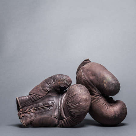 sport object: vintage boxing gloves on a gray background