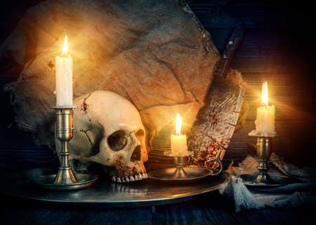 On wooden background skull and candles