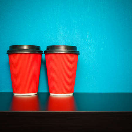 two object: two plastic cups of red on a turquoise background Stock Photo