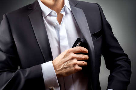 cuff links: Man pulled out of his inside jacket pocket wallet