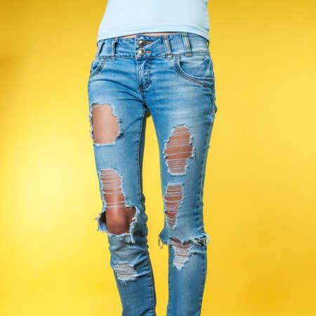 Female legs in torn jeans on an orange background