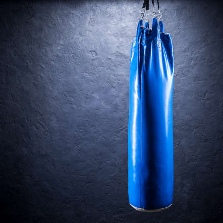 Punching bag blue against a plastered wall Stock Photo