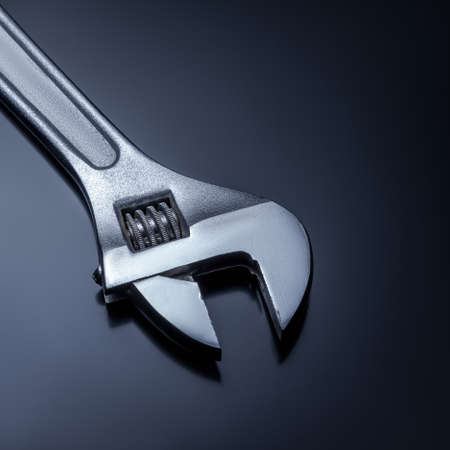 Adjustable wrench on a gray background
