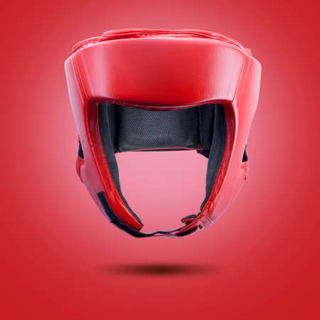 Red boxing helmet on a red background.