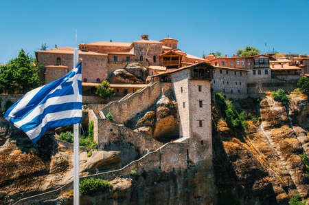 thessaly: Greek flag in front of The Holy Monastery of Great Meteoron in Meteora - complex of Orthodox monasteries on mountains, Thessaly, Greece Stock Photo