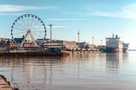HELSINKI, FINLAND - MARCH, 17, 2015: View of the Ferris wheel, the port and Viking ferry with beautiful reflection on the sea in Helsinki Finland