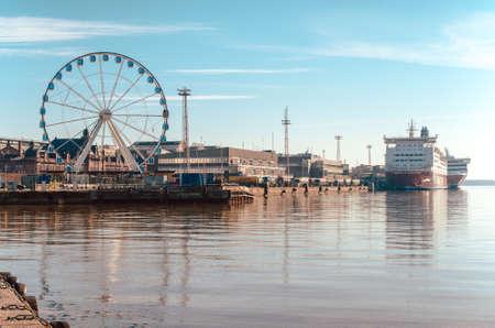 芬兰赫尔辛基——2015年3月17日:在芬兰赫尔辛基,可以看到摩天轮、港口和维京渡船,它们在海面上反射出美丽的倒影