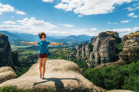 standing stone: Young happy woman stands back to the rock with raised hands. Traveler enjoying the landscape with mountain, Monasteries of Meteora, Greece Stock Photo