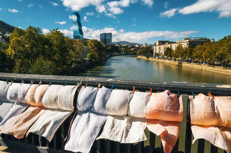 scarves: Fabrics, embroidery, scarves and underwear for sale on the railing of Dry bridge of flea market against Kura river, Biltmore Hotel and Radisson Blu Iveria Hotel in Tbilisi, Georgia.