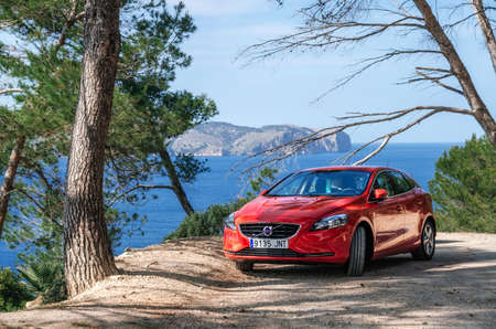 Alcudia, Mallorca, Spain - May 23, 2016: Seascape of Mediterranean Sea with a red car Volvo V40 traveling on the mountain serpentine through the pine forest along the coast of Majorca