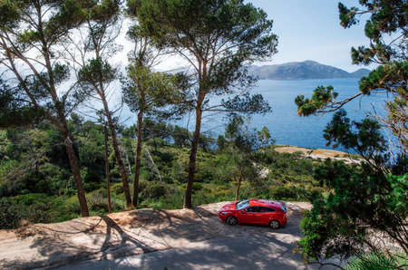 Alcudia, Mallorca, Spain - May 23, 2016: Seascape of Mediterranean Sea with a red car Volvo V40 traveling on the mountain serpentine through the pine forest along the coast of Majorca. Auto travel concept