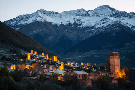mestia: View of the Svanetian towers with night illumination in Mestia village against snowy mountains at sunrise. Upper Svaneti, Georgia. Stock Photo