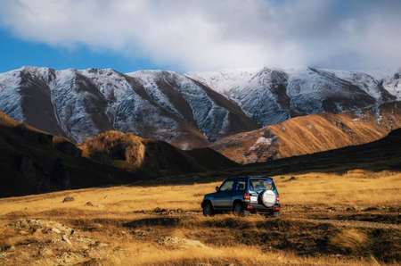 Off-road travel on car on mountain road against rocks and glacier in Caucasus, Georgia. Beautiful lights and colors at sunset