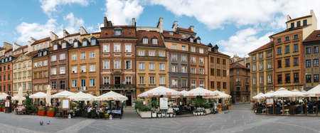 Warsaw, Poland - May 28, 2015: Panoramic view of old architecture of Warsaw. Traditional cafe with tourists against typical old houses on Old town Market square in Warsaw in a summer, Poland