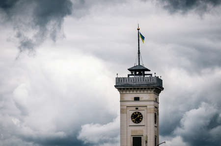 City hall clock tower of Lviv with Ukrainian flag at the top against the stormy cloudy sky, Ukraine. Concept of the restlessly or courage and power Stock Photo