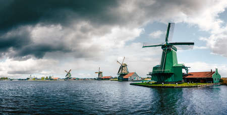 Panoramic view of Authentic Zaandam mills in Zaanstad village on the river Zaan against the stormy sky with clouds. Landmark of Netherlands.