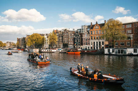 local 27: Amsterdam, Netherlands - April 27, 2017: Local people and tourists dressed in an orange clothes on the boats and in the celebration of the Kings Day.