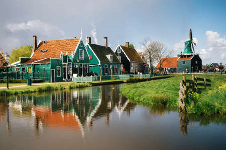 Authentic Zaandam mills and traditional vibrant houses on the water canal in Zaanstad village, Zaan river, Netherlands