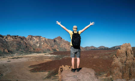 Man with a backpack stands back to the camera with raised hands. Traveler are enjoying the landscape with mountain valley of the crater of Teide volcano, Tenerife, Canary islands, Spain Stock Photo