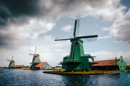 zaan: Panoramic view of Authentic Zaandam mills in Zaanstad village on the river Zaan against the stormy sky with clouds. Landmark of Netherlands.
