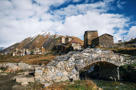 Ancient stone bridge over Enguri river and traditional Svan Towers and machub houses with flagstone in Ushguli commune, Upper Svaneti, Georgia. Georgian landmark