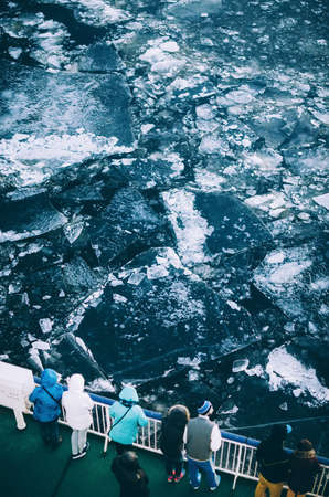 ice floe: People dressed in warm clothes stand on deck of ship and watch cracked ice floes in sea in winter