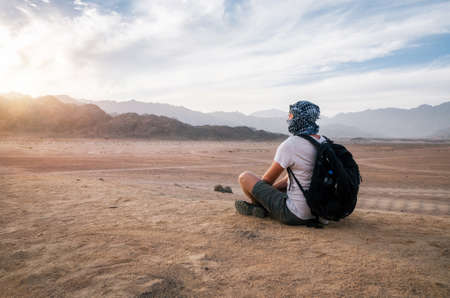 Traveler wearing arabic head scarf with a backpack sits and looks at Sinai desert and mountains at sunset, Egypt