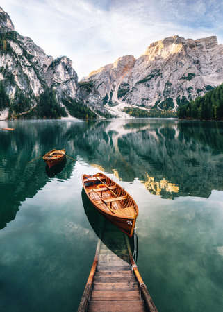 Boats and slip construction in Braies lake with crystal water in background of Seekofel mountain in Dolomites in morning, Italy Pragser Wildsee 免版税图像