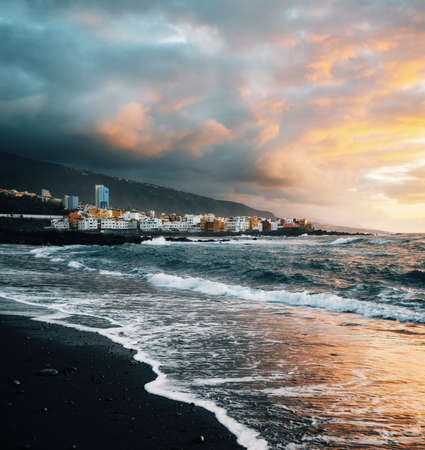 View of colorful houses of Puerto de la cruz, Jardin beach with black sand and Atlantic ocean at sunset, Tenerife, Canary islands, Spain Stock Photo