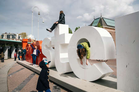 Amsterdam, Netherlands - April 27,2017: Diversity tourists interact with huge letters I Amsterdam - symbol of city. Editorial