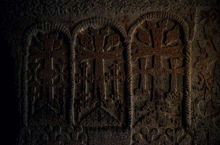 Ancient armenian cross stones khachkars ingraved in dark cave of wall of Geghard monastery